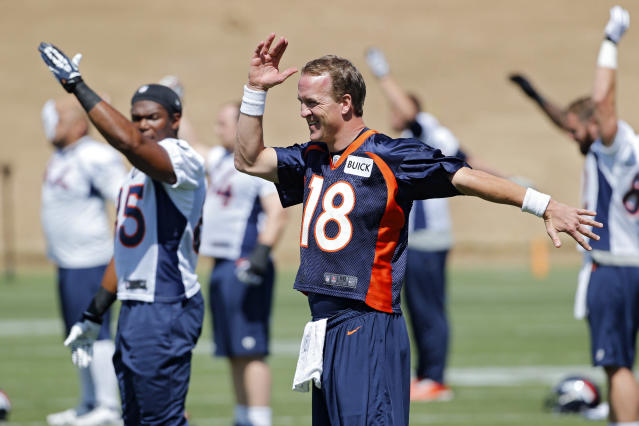 Denver Broncos quarterback Peyton Manning stretches with teammates at the NFL football teams training facility in Englewood, Colo., on Tuesday, June 10, 2014. The Broncos opened their three-day mandatory minicamp on Tuesday. (AP Photo/Ed Andrieski)