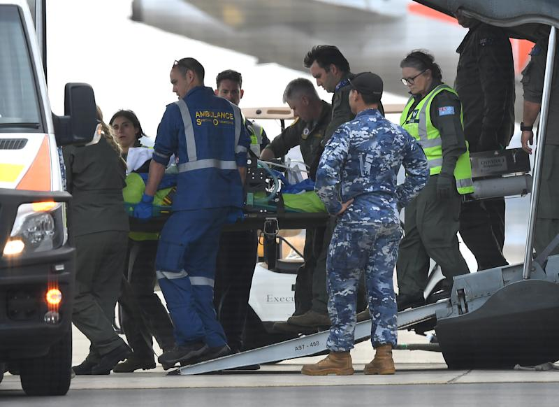A survivor of the fatal Whaakaari Volcanic eruption in New Zealand is removed on a stretcher from a RAAF C-130 Hercules at Sydney Airport in Sydney, Thursday, December 12, 2019.