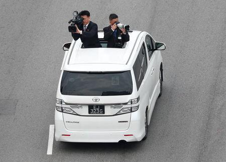 FILE PHOTO: Official cameramen follow the motorcade of North Korean leader Kim Jong Un travels towards Sentosa for his meeting with U.S. President Donald Trump, in Singapore June 12, 2018. REUTERS/Edgar Su/File Photo