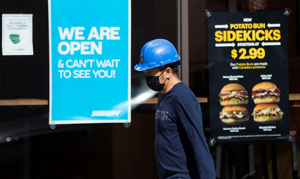 TORONTO, March 12, 2021 -- A worker wearing a face mask walks past a fast food restaurant with a