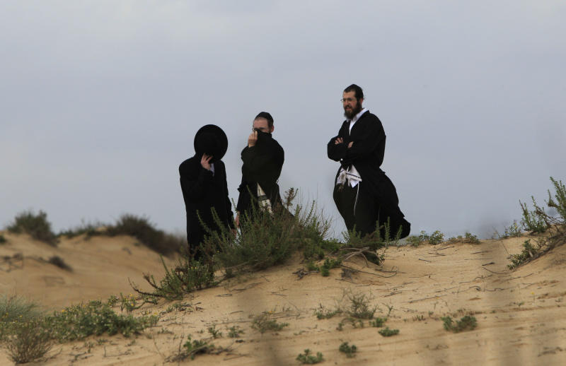 Israeli Jewish Orthodox Jews gather near the site where a rocket, fired by Palestinian militants from the Gaza Strip, landed in the southern Israeli city of Ashdod, Thursday, March 24, 2011. Israeli aircraft struck the Gaza Strip on Thursday in response to militant rocket and mortar attacks, stoking concerns that a grave new round of hostilities will fill the vacuum left by an impasse in Israeli-Palestinian peacemaking. (AP Photo/Tsafrir Abayov)