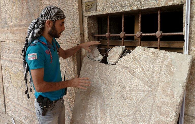 A Syrian rebel fighter inspects a mosaic at the Alma Arra museum in Maarat al-Numan in October