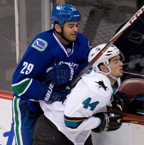 Vancouver Canucks' Tom Sestito, left, checks San Jose Sharks' Marc-Edouard Vlasic during the second period of an NHL hockey game, Thursday, Oct. 10, 2013 in Vancouver, British Columbia. (AP Photo/The Canadian Press, Darryl Dyck)