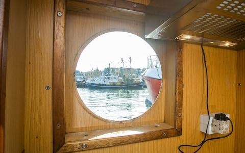 A smashed window onboard of Golden Promise at the Brixham Harbour in Devon, which was smashed by a rock thrown by french fishermen - Credit: SWNS.com