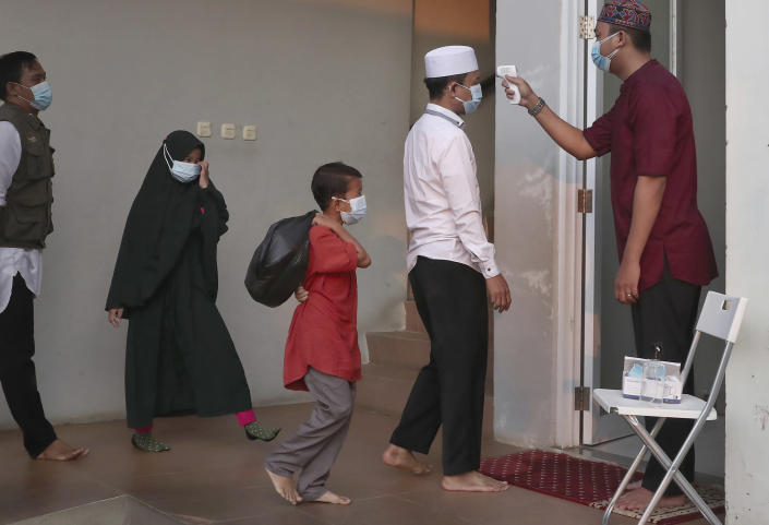 An official takes the body temperature reading of worshippers arriving for an Eid al-Adha prayer as to curb the spread of coronavirus during an Eid al-Adha prayer at Zona Madina mosque in Bogor, Indonesia, Tuesday, July 20, 2021. Muslims across Indonesia marked a grim Eid al-Adha festival for a second year Tuesday as the country struggles to cope with a devastating new wave of coronavirus cases and the government has banned large gatherings and toughened travel restrictions. (AP Photo/Tatan Syuflana)