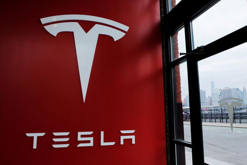 FILE PHOTO: A Tesla logo is painted on a wall inside of a Tesla dealership in New York
