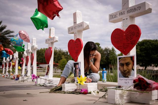 <p>A woman writes a note on a cross for Eric Ivan Ortiz-Rivera at a memorial with wooden crosses for each of the 49 victims of the Pulse Nightclub, next to the Orlando Regional Medical Center, June 17, 2016 in Orlando, Florida. (Drew Angerer/Getty Images) </p>