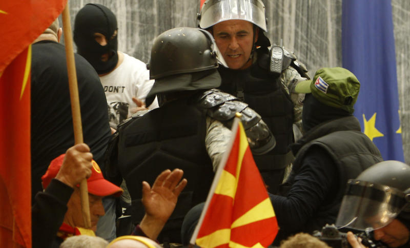 Police try to block protestors from entering into the parliament building in Skopje, Macedonia, Thursday, April 27, 2017. Scores of protesters broke through a police cordon and entered Macedonian parliament to protest the election of a new speaker despite a months-long deadlock in talks to form a new government. (AP Photo/Boris Grdanoski)