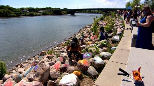 Youth from Chokecherry Studios painted 215 stones after unmarked graves believed to contain the remains of 215 children were found at the site of the former residential school in Kamloops, B.C.  (Chanss Lanagan/CBC - image credit)