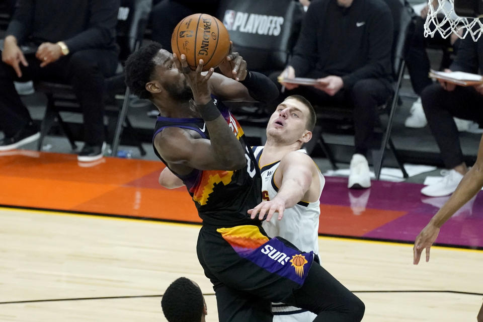 Phoenix Suns center Deandre Ayton is fouled by Denver Nuggets center Nikola Jokic, right, during the second half of Game 1 of an NBA basketball second-round playoff series, Monday, June 7, 2021, in Phoenix. (AP Photo/Matt York)