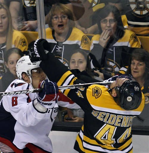 Boston Bruins defenseman Dennis Seidenberg (44) gets a stick to the face from Washington Capitals left wing Alex Ovechkin (8) during the second period of Game 2 of an NHL hockey Stanley Cup first-round playoff series in Boston, Saturday, April 14, 2012. AP Photo/Charles Krupa)