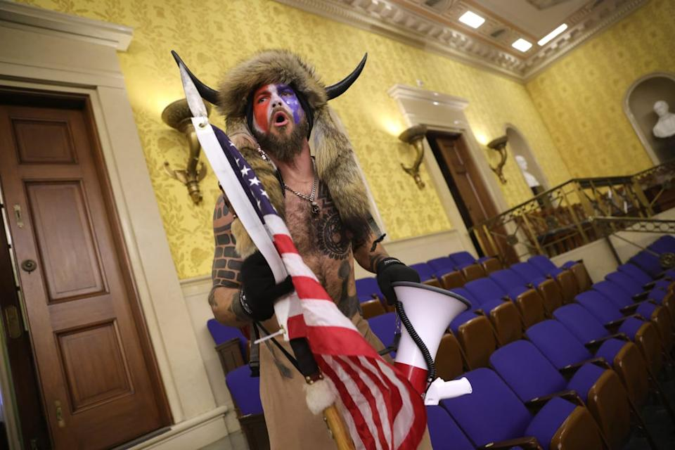 """<div class=""""inline-image__caption""""><p>Jake Angeli was photographed inside the Senate chamber on Wednesday.</p></div> <div class=""""inline-image__credit"""">Win McNamee/Getty</div>"""