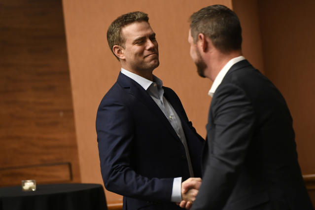 Chicago Cubs president of baseball operations Theo Epstein left, shakes hands with former Cubs pitcher Travis Wood right, during the baseball team's convention, Friday, Jan. 17, 2020, in Chicago. (AP Photo/Paul Beaty)