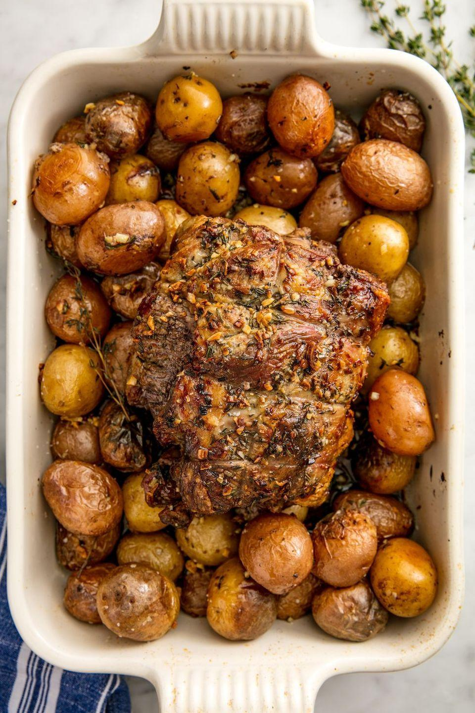 """<p>Hacking your way through roasting a carved protein to serve at the dinner table has never been so easy. This tender cut of lamb is propped up among well-seasoned potatoes that sizzle in the natural juices of the lamb, allowing it to be evenly roasted. </p><p><em><a href=""""https://www.delish.com/cooking/recipe-ideas/recipes/a56354/best-roast-lamb-recipe/"""" rel=""""nofollow noopener"""" target=""""_blank"""" data-ylk=""""slk:Get the recipe from Delish »"""" class=""""link rapid-noclick-resp"""">Get the recipe from Delish »</a></em></p>"""