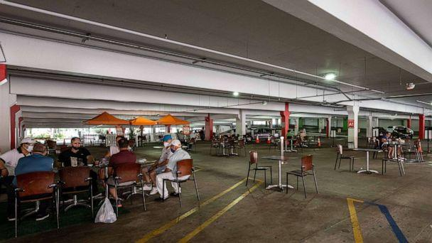PHOTO: People dine in the parking garage dining area at the Glendale Galleria parking structure in Los Angeles, Aug. 11, 2020. (Rob Latour/REX via Shutterstock)