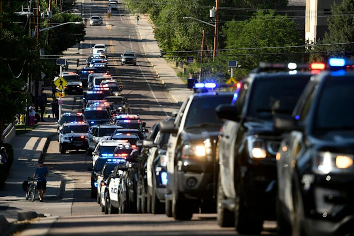 Dozens of police vehicles line up to take part in a procession held in the aftermath of a shooting in Olde Town Arvada that took the life of a police officer on Monday, June 21, 2021 in Arvada, Colo.