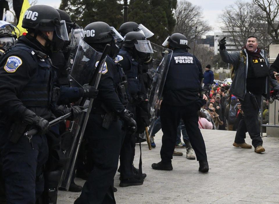 """<div class=""""inline-image__caption""""><p>Russell Taylor, right, is photographed flipping off cops at the U.S. Capitol on Jan. 6.</p></div> <div class=""""inline-image__credit"""">Andrew Caballero-Reynolds/Getty</div>"""