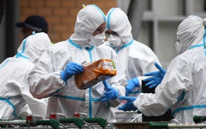 A loaf of bread is passed between officials in protective suits in the Australian city of Melbourne