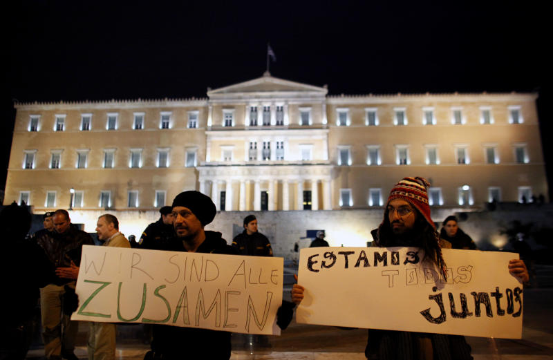 """Protesters hold placards that read in Italian and German """" we are all together"""" in front of the Greek Parliament in Athens on Saturday, Feb. 18 2012. A few hundred protesters gathered in front of the Greek Parliament to protest against austerity measures. (AP Photo/Kostas Tsironis)"""