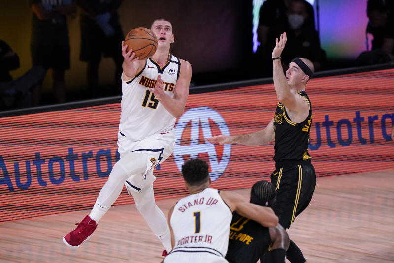 Denver Nuggets' Nikola Jokic (15) drives to the basket around Los Angeles Lakers' Alex Caruso, right, during the second half of an NBA conference final playoff basketball game Sunday, Sept. 20, 2020, in Lake Buena Vista, Fla. (AP Photo/Mark J. Terrill)