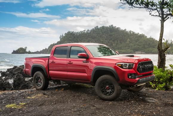 A red Toyota Tacoma 4x4 parked next to a lake.