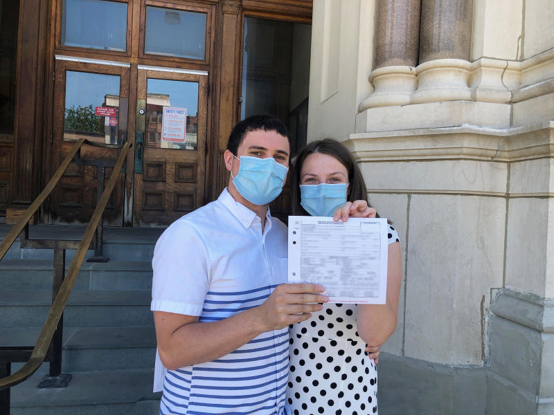 The bride and groom with their marriage license. (Courtesy of Erin Farley)