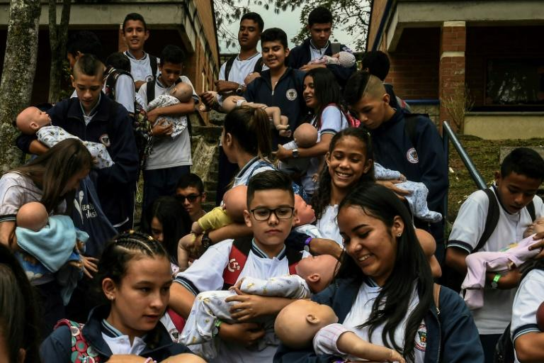 """Students carry their """"babies"""" during a break at a school in Caldas municipality, Colombia on May 17, 2019 (AFP Photo/JOAQUIN SARMIENTO)"""