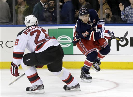 New York Rangers' Ryan Callahan, right, shoots past New Jersey Devils' Anton Volchenkov during the second period of an NHL hockey game on Sunday, April 21, 2013, in New York. (AP Photo/Seth Wenig)