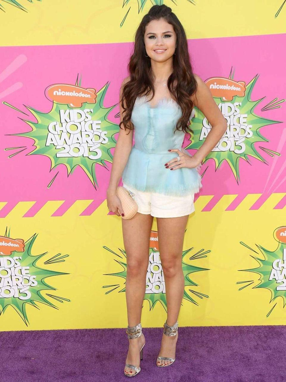 <p>Selena Gomez poses for the cameras at the Kids Choice Awards wearing a peplum top paired with white shorts by Oscar de la Renta, March 2013.</p>