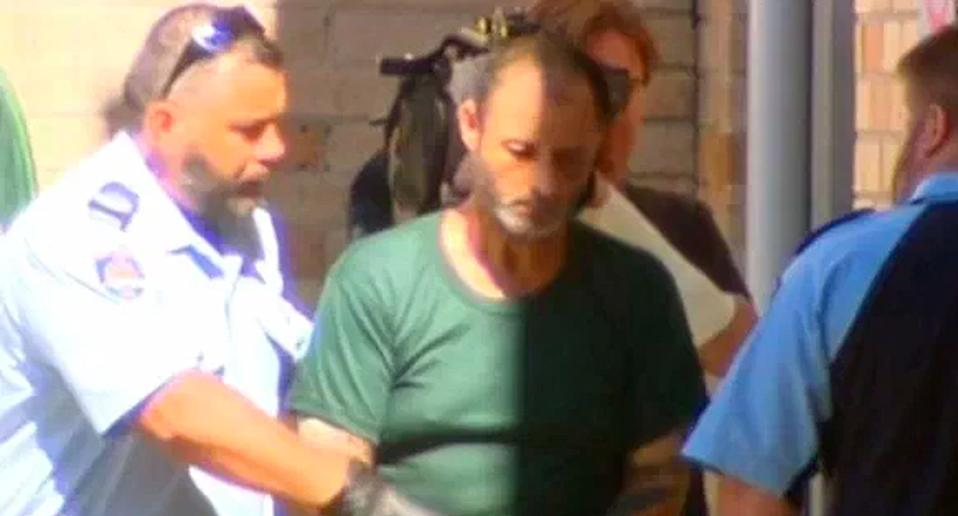 Anthony Sampieiri is pictured in a green shirt flanked by police.