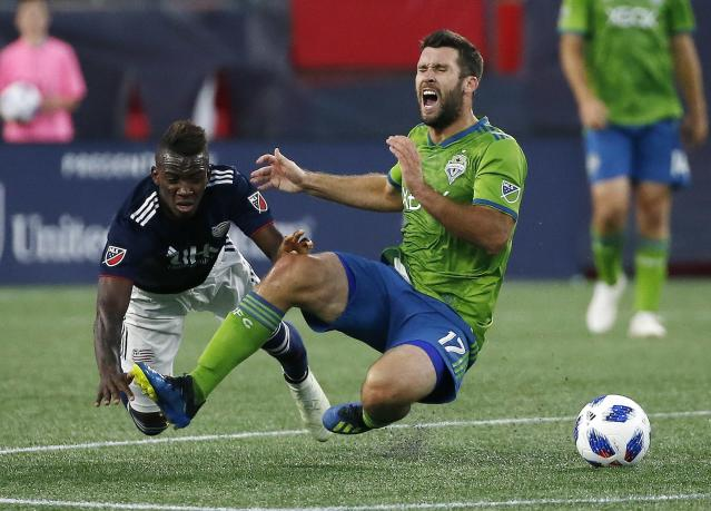 Seattle Sounders' Will Bruin (17) and New England Revolution's Luis Caicedo go down while battling for the ball during the first half of an MLS soccer game in Foxborough, Mass., Saturday, July 7, 2018. (AP Photo/Michael Dwyer)
