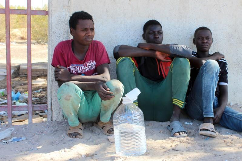 Migrants are seen on the street, after being rescued by the Libyan coast guard, in Misrata