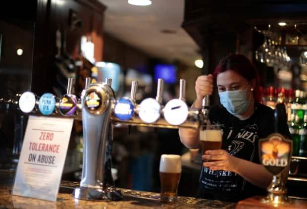 A woman pours beer into a glass at The Fox on the Hill pub as it reopens while COVID-19 restrictions continue to ease, in London on May 17, 2021.
