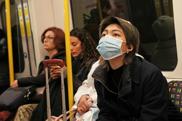 With a coronavirus Covid-19 case confirmed in London, an underground passenger is pictured wearing a mask. (Getty Images)
