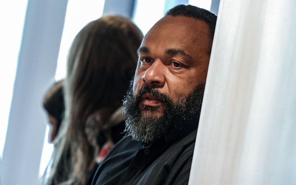 In this file photo taken on March 26, 2019 controversial French comic Dieudonne M'bala M'bala looks on as he arrives at the Paris courthouse - KENZO TRIBOUILLARD/AFP