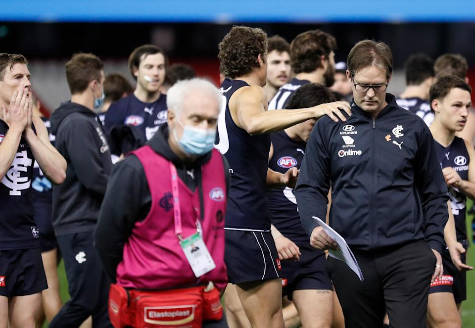 David Teague, Senior Coach of the Blues, is consoled by Charlie Curnow at three quarter time during the 2021 AFL Round 23 match.