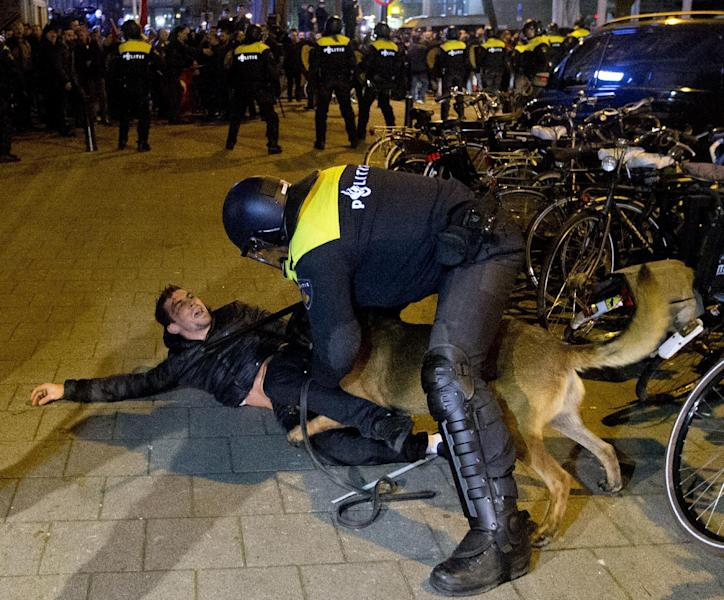 "A Dutch riot policeman tries to get his dog to let go of a man after riots broke out during a pro Erdogan demonstration at the Turkish consulate in Rotterdam, Netherlands, Sunday, March 12, 2017. Turkish Foreign Minister Mevlut Cavusoglu was due to visit Rotterdam on Saturday to campaign for a referendum next month on constitutional reforms in Turkey. The Dutch government says that it withdrew the permission for Cavusoglu's plane to land because of ""risks to public order and security."" (AP Photo/Peter Dejong)"