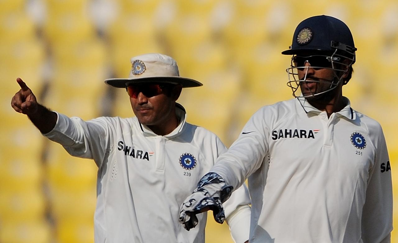 India's cricket team captain Mahendra Singh Dhoni (R) and Virender Sehwag celebrate after the wicket of New Zealand's Gareth Hopkins (not pictured) during the third Test cricket   match at The Vidarbha Cricket Association, Jamtha Stadium in Nagpur on November 20, 2010.