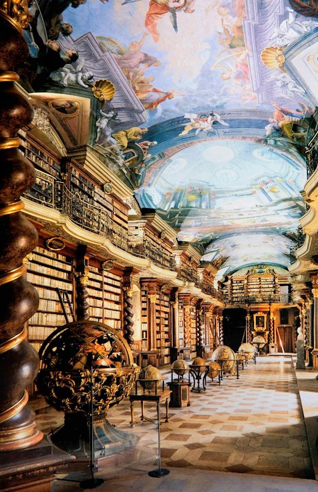 """<p>With its ornate ceiling frescoes by Jan Hiebl and rich gold and mahogany spiral pillars, it's no wonder why the <a href=""""https://www.klementinum.com/prohlidky/baroque-library/"""">Klementinum</a> is touted as """"the Baroque pearl of Prague."""" The library first opened in 1722 as a part of a Jesuit university, but now serves as the National Library of the Czech Republic, housing over 20,00 volumes of foreign theological literature. A portrait of Emperor Joseph II sits at the head of the hall to commemorate his work in preserving books from abolished monastic libraries, many of which remain in the hall today.</p>"""
