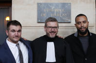 Alek Skarlatos, left, Anthony Sadler, right, and their lawyer Thibault de Montbrial, pose for photographers at the end of their hearing during the Thalys attack trial at the Paris courthouse, Friday, Nov. 20, 2020. Passengers who wrestled and disarmed an Islamic State gunman aboard a high-speed Amsterdam to Paris train are recounting how their split-second decisions helped prevent what could have become a mass slaughter. (AP Photo/Francois Mori)