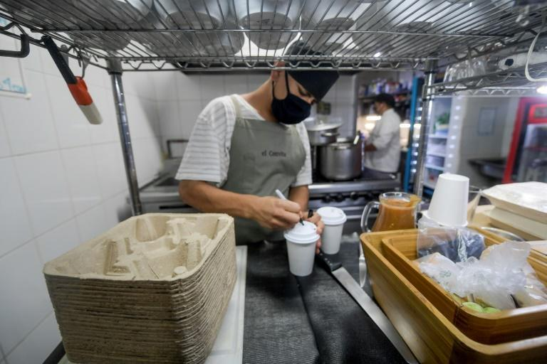 A restaurant worker prepares drinks using biodegradable packaging in Mexico City, which is banning many single-use plastics