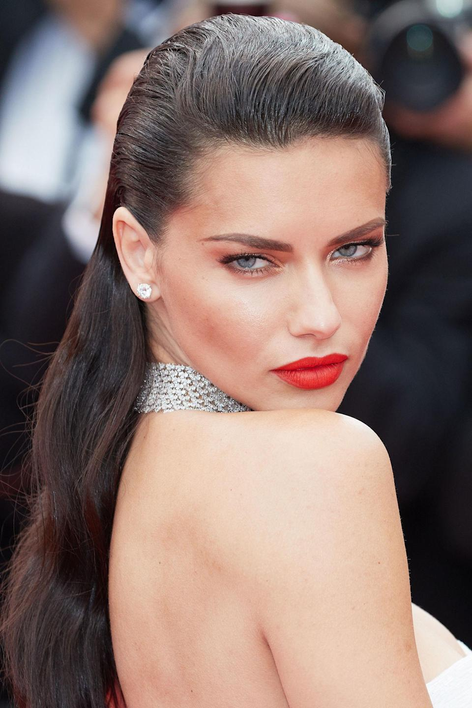 <p>Wearing her long hair slicked back with a simple white gown, Lima's orangey red lip took the main focus. </p>