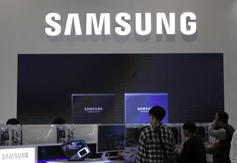 Visitors tour near the logo of Samsung Electronics at semiconductor exhibition in Seoul, South Korea, Tuesday, Oct. 8, 2019. Samsung Electronics has predicted its operating profit for the last quarter will fall by more than 56% from a year earlier amid sluggish global demand for computer chips. (AP Photo/Lee Jin-man)