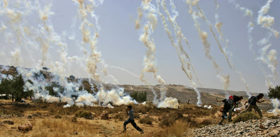 <p>Demonstrators run to avoid tear gas canisters fired by Israeli troops during a demonstration against Israel's separation barrier in the West Bank village Bilin, near Ramallah, June 6, 2008. (Photo: Muhammed Muheisen/AP) </p>