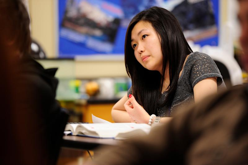 In this Feb. 27, 2012, photo, Sally Kim takes notes during a physics class at Columbia Independent School in Columbia, Mo. Kim's parents, who live in South Korea, sent her to live with relatives in Columbia for a better education that provides more collegiate opportunities. Such relocations, known as early study abroad, have surged in popularity in South Korea, where a rigid, test-driven education system, combined with intense social pressure to succeed in an English-first global economy, often means breaking up families for the sake of school. (AP Photo/Grant Hindsley)
