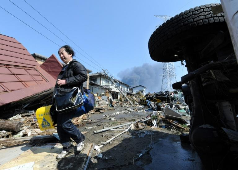 A local resident collects his son's school bags from a collapsed house in Miyagi prefecture