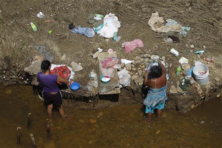 Women wash clothes next to a river in Coyuca de Benitez on the outskirts of Acapulco