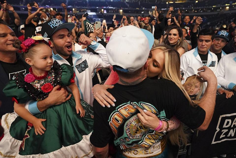 Canelo Álvarez kisses his girlfriend in the crowd as someone holds up a little girl with flowers in her hair