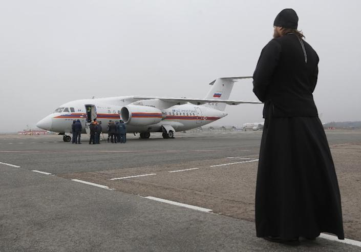 A Russian Orthodox priest looks on as the bodies of victims of the Sinai plane are flown back to St. Petersburg, on November 6, 2015 (AFP Photo/Dmitry Lovetsky)
