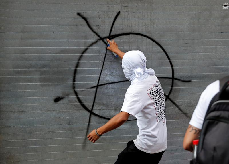 A demonstrator sprays graffiti during a march marking the 51st anniversary of the 1968 student massacre by Mexican armed forces, in Mexico City, Mexico October 2, 2019. REUTERS/Henry Romero